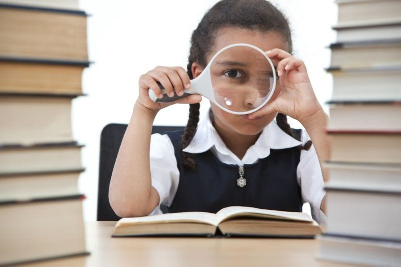 Girl examining books with a magnifying glass